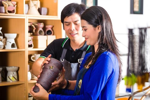Klant in een aziatische aardewerkwinkel Premium Foto