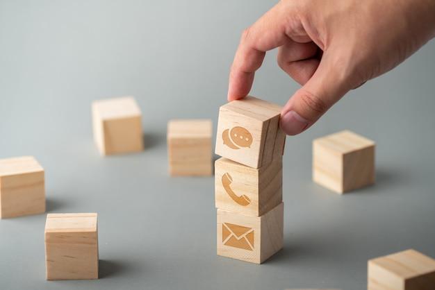 Klantenservice & contacteer ons pictogram op het kubus houten toetsenbord Premium Foto