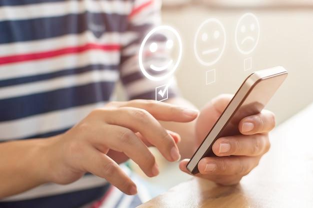 Klantenservice-ervaring en onderzoek naar bedrijfstevredenheid. het close-upbeeld van mannelijke handen die mobiele smartphone gebruiken kiest gezichtsglimlach Premium Foto
