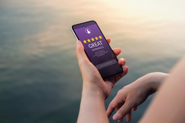 Klantervaringen concept. five stars rating en positive review worden op het scherm van de smartphone getoond Premium Foto