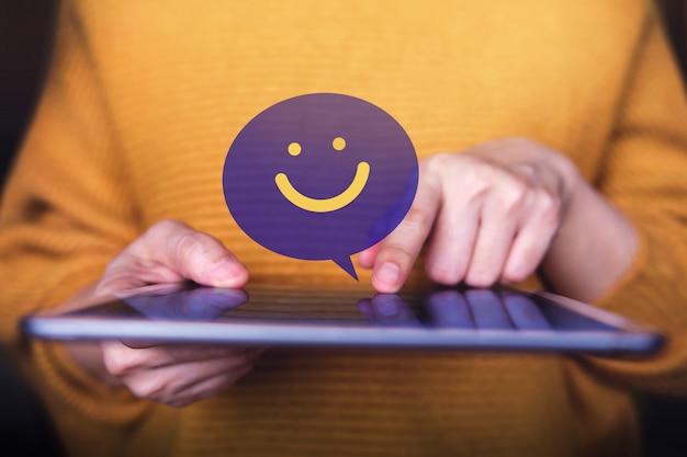 Klantervaringen concept. tevreden klant die digitale tablet gebruikt voor het verzenden van een positieve beoordeling. satisfaction online survey Premium Foto