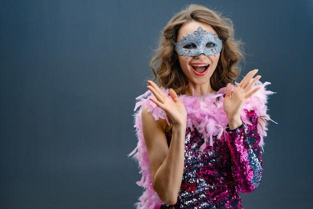 Klap in je handen enthousiaste jonge vrouw in een glanzende paarse jurk met een boa in de nek Premium Foto