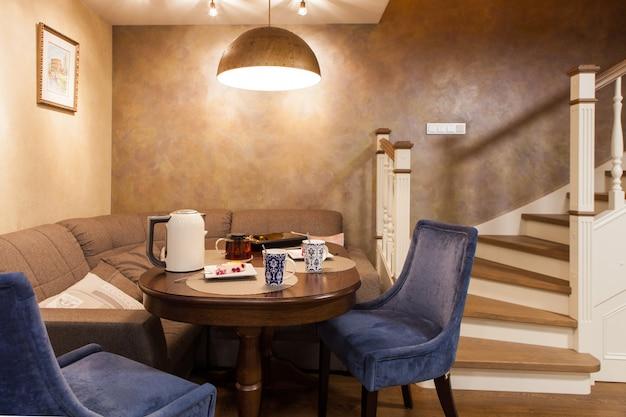 Klassiek interieur van een gastenkamer in een appartement met twee verdiepingen. eettafel en stoelen, wit houten trap naar de tweede verdieping met ingebouwde lockers. Premium Foto