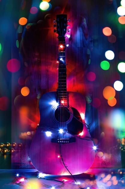 Klassieke akoestische gitaar in kerstvakantie lichten ter nagedachtenis aan muziek Premium Foto