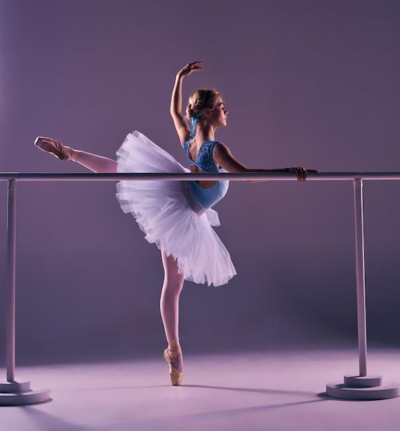 Klassieke ballerina poseren op ballet barre Gratis Foto