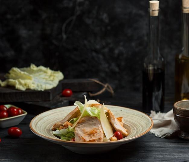 Klassieke caesarsalade met visfilet en parmezaanse kaas bovenop Gratis Foto