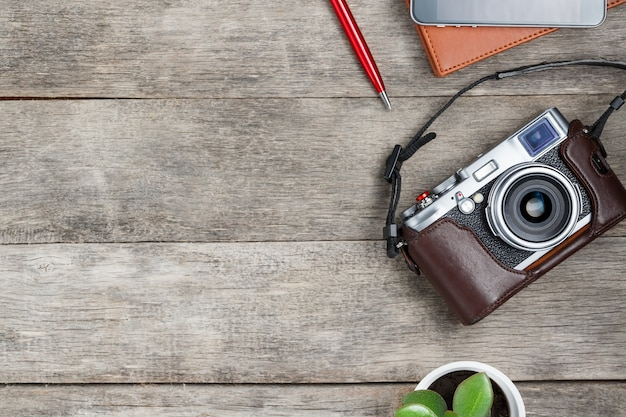 Klassieke camera, met een bruin notitieblok, een rode pen, een telefoon en groene groei. conceptenlijst voor een reisfotograaf Premium Foto