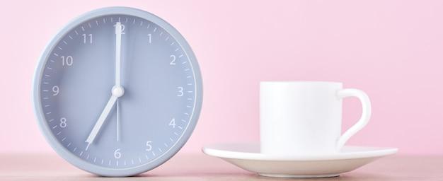 Klassieke grijze wekker en witte koffiekop op een roze achtergrond, lange banner Premium Foto
