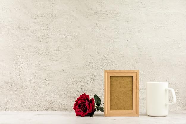 Klassieke houten fotolijst en rode roos met een witte koffiekop. Premium Foto