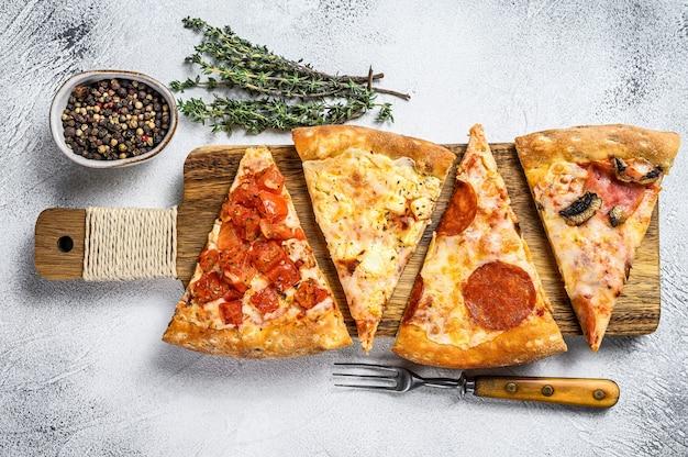 Klassieke italiaanse pizza op een houten snijplank. witte achtergrond. bovenaanzicht. Premium Foto