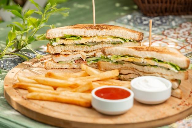 Klassieke kip club sandwich met frietjes Gratis Foto