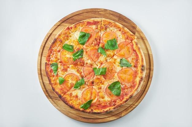 Klassieke pizzamargarita met rode saus, tomaten en basilicum op een houten dienblad. witte achtergrond. italiaanse keuken Premium Foto