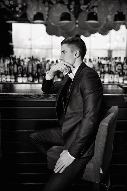 Klassieke trouwfoto. portret van een bruidegom zittend op een stoel bij de bar. low key. Premium Foto