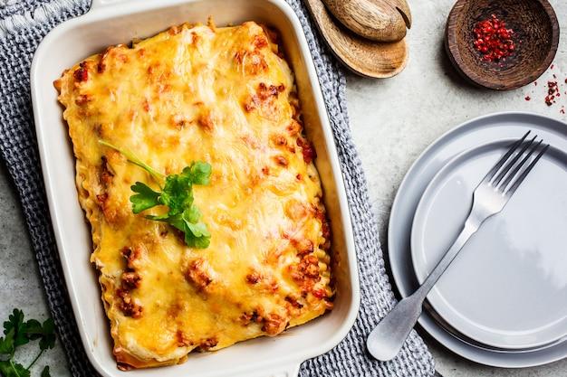 Klassieke vleeslasagna's met kaas in ovenschotel op lichtgrijs Premium Foto