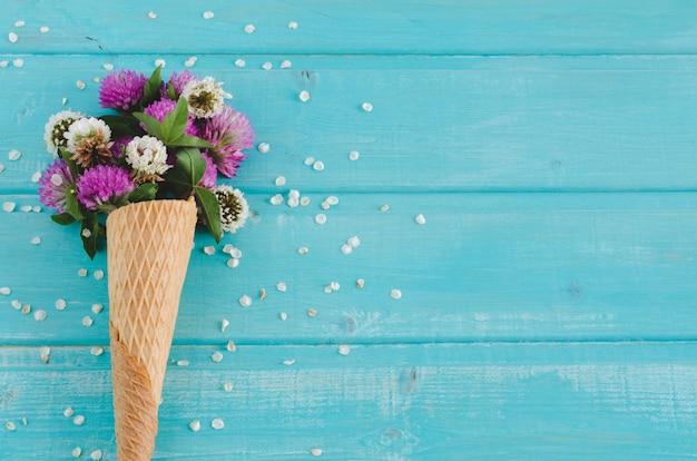Klaverbloemen in kegel voor roomijs op blauwe achtergrond. bovenaanzicht. Premium Foto