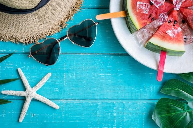 Kleding met accessoires en tropische vruchten en bloemen op witte houten achtergrond in de zomer Premium Foto