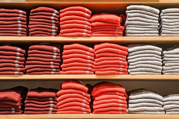 Kleding wordt in de winkel getoond. veel warme truien met felle kleuren worden netjes op een rij op de winkelschappen gestapeld. stapels veelkleurige gebreide wollen kleding. t-shirt op de plank. Premium Foto