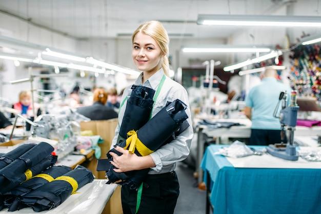 Kledingontwerper stof textielmaterialen in handen houden, vervaardigen op naai-fabriek. jurk curve meten, naaister, kleermakerij of maatwerk Premium Foto