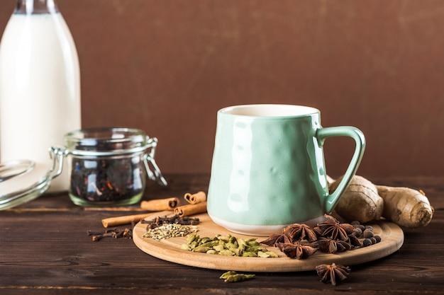 Kleikop op een houten raad op een donkere achtergrond. een kopje masalathee. specerijen kruidnagel, venkel, kaneel, kardemom, melk. Premium Foto