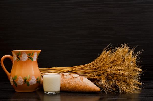 Kleikruik, een glas melk, roggebrood en een schoof op een zwarte achtergrond Premium Foto