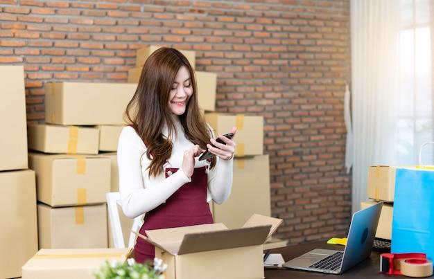 Klein bedrijf opstarten ondernemer mkb of freelancevrouw die met dozen thuis of op kantoor werken. afhandelen van bezorgpakketten Premium Foto