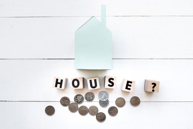 Klein blauw document huismodel met brieven houten blokken en muntstukken op witte houten lijst Gratis Foto