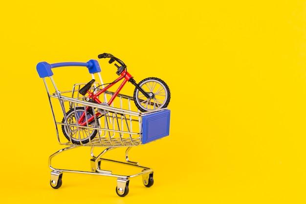 Klein fietsstuk speelgoed in het boodschappenwagentje tegen gele achtergrond Gratis Foto