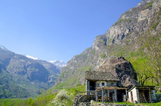 Klein gebouw op de berg omgeven door rotsen bedekt met groen in ticino in zwitserland Gratis Foto