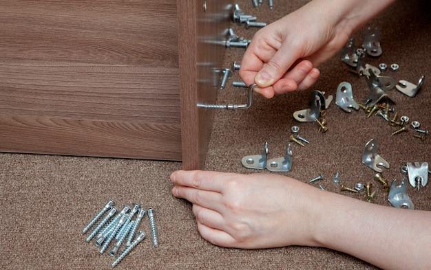 Klein gereedschap voor het monteren van meubels, meubelbeugels en bevestiging, close-up handvast schroeven met inbussleutel. Premium Foto