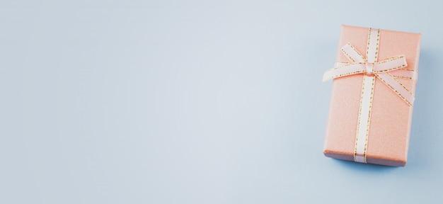 Klein geschenk op een pastel achtergrond, close-up. geschenkdoos met een strik Premium Foto