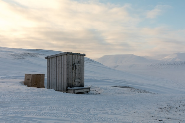 Klein houten bijgebouw hut in het midden van het noordpoollandschap in de winter Premium Foto