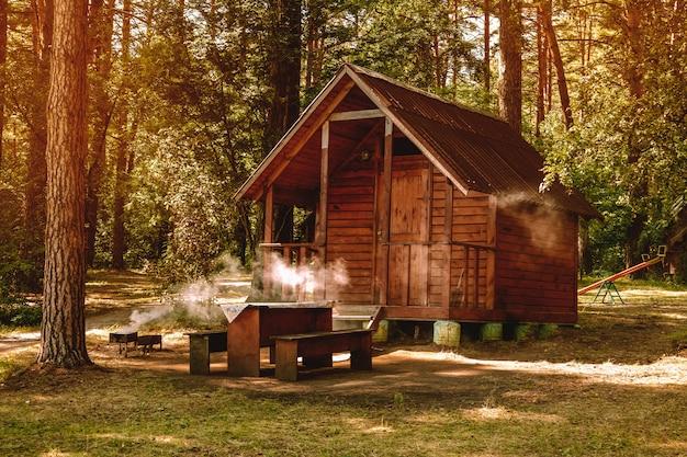 Klein houten huis in een dennenbos voor recreatie, kamperen in het bos, barbecue in de natuur Premium Foto