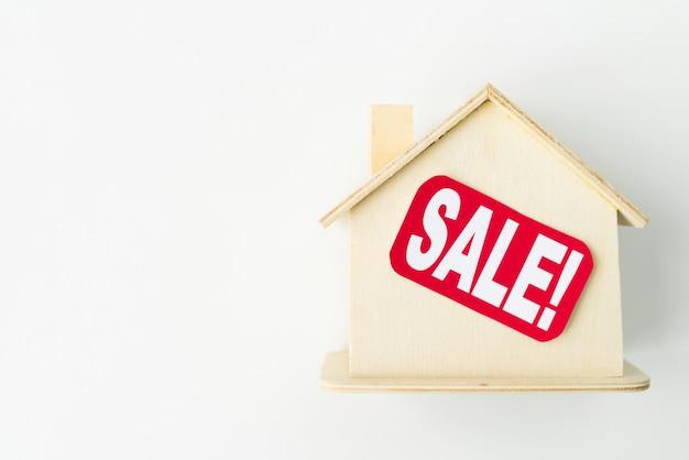Klein houten huis met verkoopteken Gratis Foto