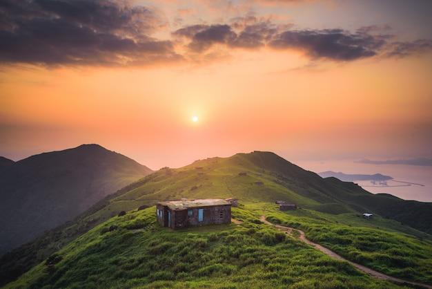 Klein huis gebouwd op een rustige groene heuvel hoog in de bergen Gratis Foto