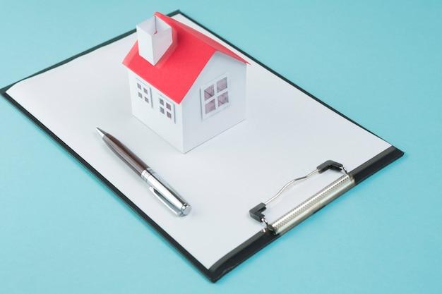 Klein huismodel en pen op leeg klembord over blauwe achtergrond Gratis Foto