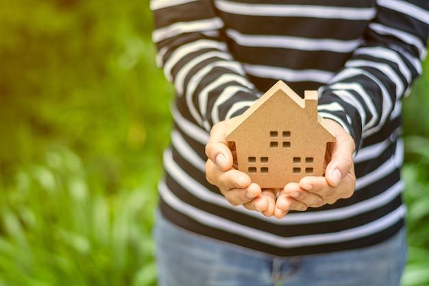 Klein huismodel in vrouwenhand. Premium Foto