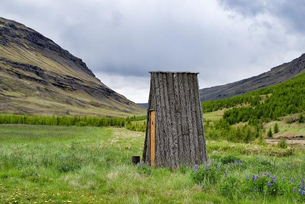 Klein ijslands blokhut zonder ramen, in een weiland naast bergen. zonder muren. alleen dak. Premium Foto