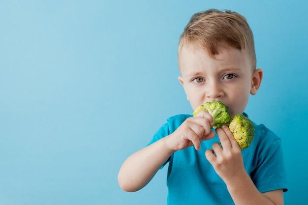 Klein kind bedrijf broccoli in zijn handen op blauwe achtergrond. veganistisch en gezond concept Premium Foto