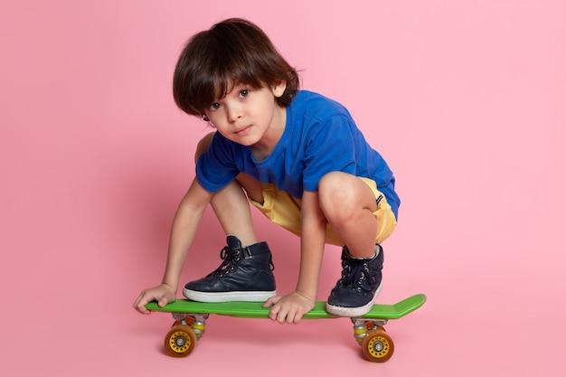 Klein kind jongen in blauw t-shirt rijden op skateboard op roze muur Gratis Foto
