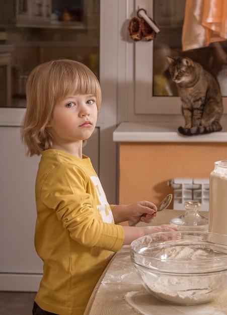 Klein kind koken in de keuken. Premium Foto