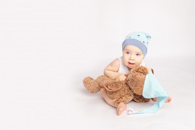 Klein kind met een teddybeer op een witte geïsoleerde achtergrond Premium Foto