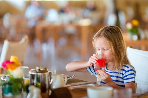 Klein kind ontbijten op terras. aanbiddelijk meisje die vers watermeloensap drinken die van ontbijt genieten. Premium Foto