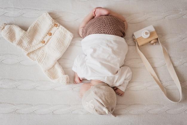 Klein kind slaapt naast de wintertrui Gratis Foto