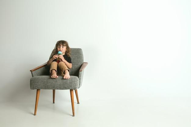 Klein kind zitten en spelen in fauteuil geïsoleerd op witte ruimte. een jonge jongen met blond haar kijkt geïnteresseerd in de wereld om hem heen Gratis Foto