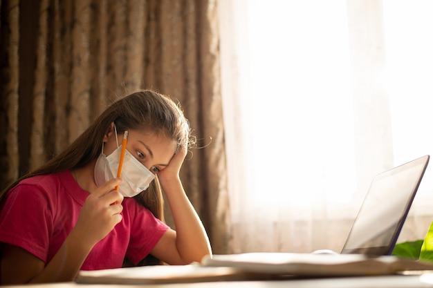 Klein meisje dat in medisch masker thuis bestudeert. ijverig student denken, oefeningen doen, huiswerk voorbereiden Premium Foto