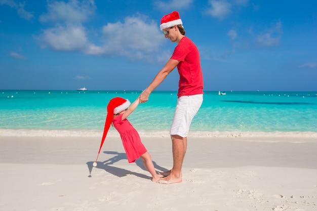 Klein meisje en gelukkige vader in santa hat hebben plezier op tropisch strand Premium Foto