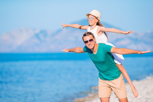 Klein meisje en gelukkige vader plezier tijdens strandvakantie Premium Foto