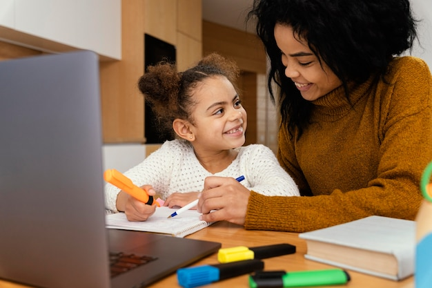 Klein meisje en grote zus thuis tijdens online school Premium Foto
