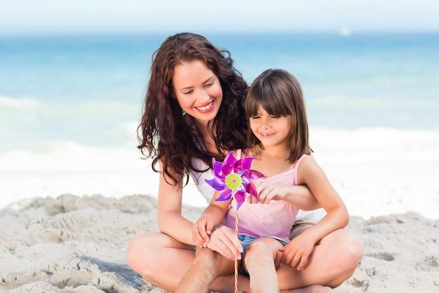 Klein meisje en haar moeder met een windmolen Premium Foto