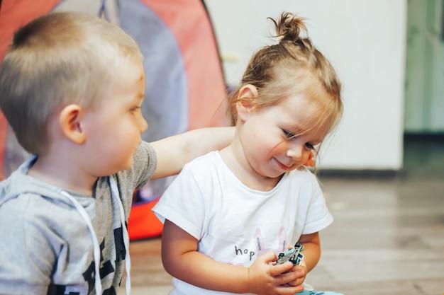 Klein meisje en jongen knuffel thuis Premium Foto